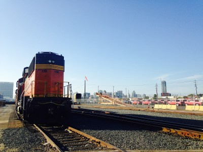 The San Diego skyline peaks out from behind railroad tracks cutting through Barrio Logan. Photo by Torrey Bailey