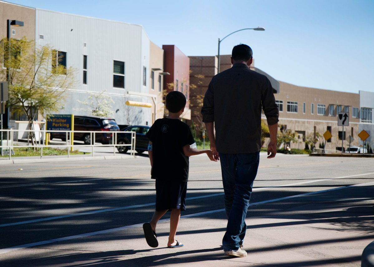 A father walks with his son outside of Rady Children's Hospital, one of the medical providers who recently experienced a data breach. Jan. 9, 2016. Megan Wood, inewsource.