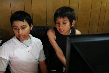 Fernanda and Robert Sandoval play games on their fathers computer while he finishes his workday. April 21, 2016. Megan Wood, inewsource.