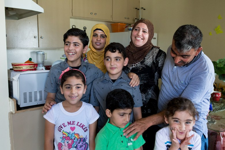 Mohamad Abdullah (far right), touches the shoulder of his son during a family photo in kitchen of the family's two-bedroom El Cajon apartment, July 25, 2017. Photo by Megan Wood, inewsource.