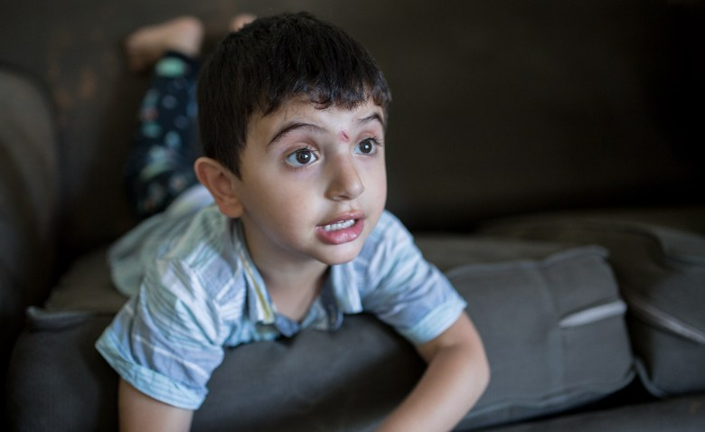One of Mostafa Inezan's sons plays on the couch in the family's new three-bedroom apartment, July 25, 2017. Photo by Megan Wood, inewsource.