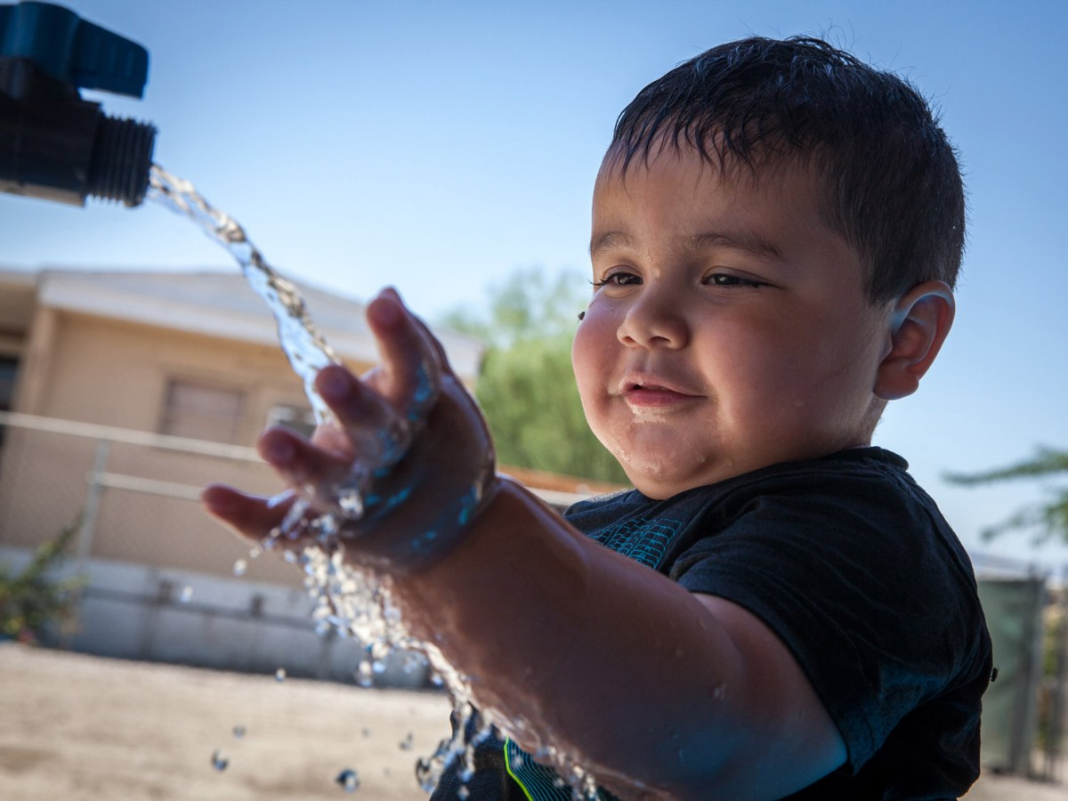 Axel Ruiz, 2, plays with arsenic-contaminated water at his family's home in St. Anthony Mobile Home Park in California. (Maria Esquinca/News21)