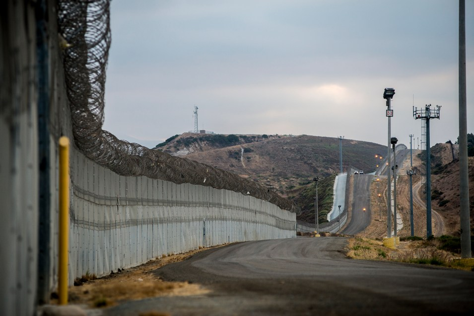 <small>Stretches of secondary fencing are topped with spirals of concertina wire along the U.S.-Mexico border between the San Ysidro and Otay Mesa ports of entry, in San Diego on Aug. 16, 2017. Border Patrol agents use the frontage road between this and primary fencing to patrol for immigrants attempting to enter the U.S. illegally. <em>(Brandon Quester/inewsource)</em><small>