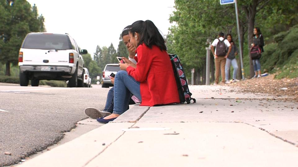 Roosevelt Middle School students wait for a North County Transit District Bus on North Santa Fe Avenue in Vista, June, 6, 2017. (Video screenshot by Katie Schoolov/KPBS)