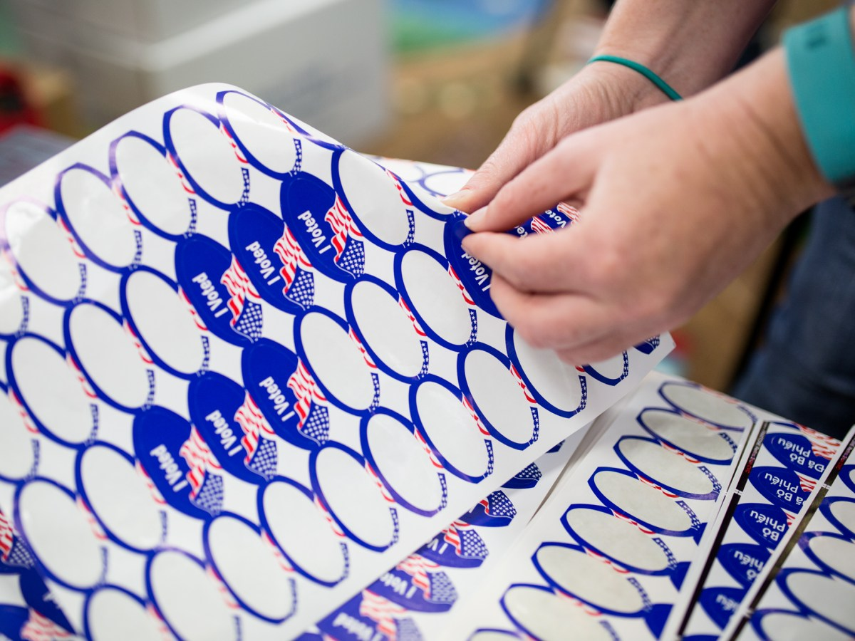 A poll worker at the North Park Library is shown handing out stickers to voters on June 5, 2018. (Megan Wood/inewsource)