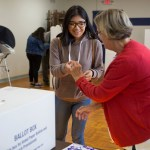 A poll worker hands out stickers at the San Ysidro Library on Election Day.