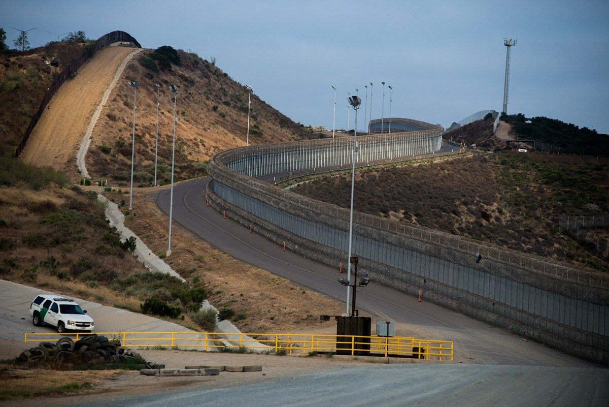 Two layers of fencing, one covered in concertina wire, follow a road near the San Ysidro Port of Entry in San Diego on Aug. 16, 2017.