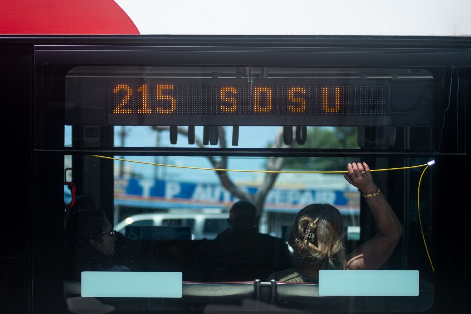 A bus rider prepares for a stop on the Mid-City Rapid 215 route on El Cajon Boulevard in San Diego on April 26, 2019. (Brandon Quester/inewsource)