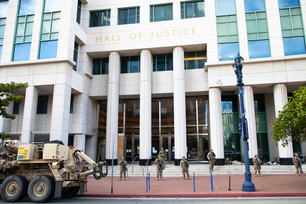 California National Guard troops stand on the steps of the Hall of Justice as a San Diego protest over the killing of George Floyd and other black men and women by police walks down Broadway, June 6, 2020. Homeless residents are lying near the entry to the building.