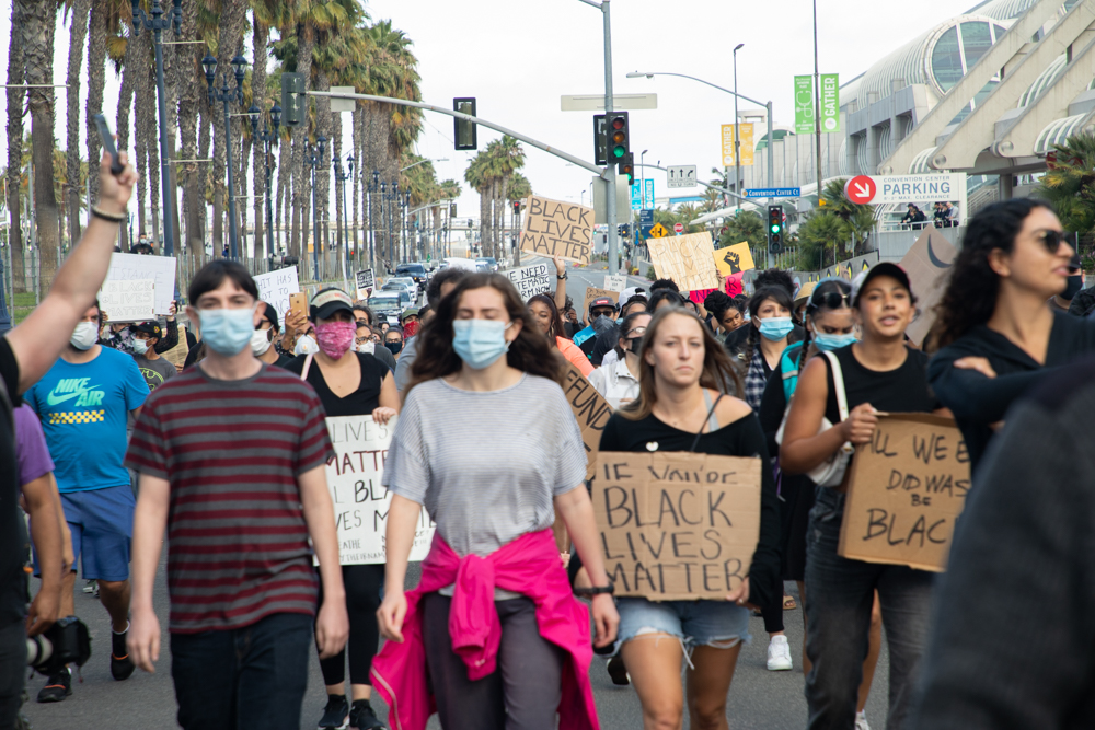 Demonstrators protesting the killing of George Floyd and other black men and women by police walk by the San Diego Convention Center where police were standing guard, June 6, 2020.