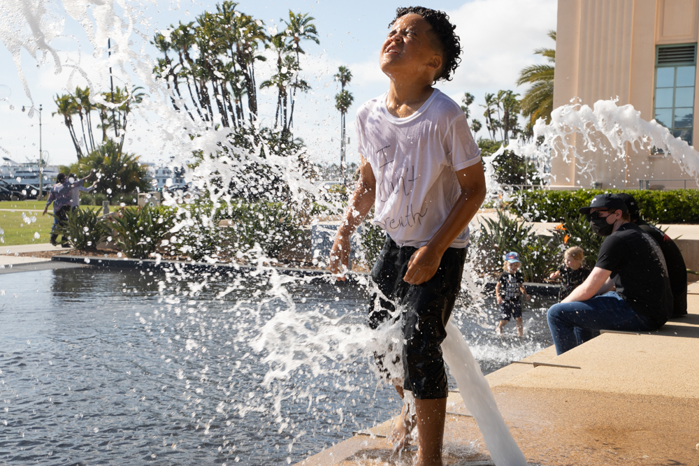 Jakobi Johnson, 9, plays in the fountains at the Waterfront Park in San Diego during protests over the killing of George Floyd and other black men and women by police, June 6, 2020. Jakobi was at the protest with his family.