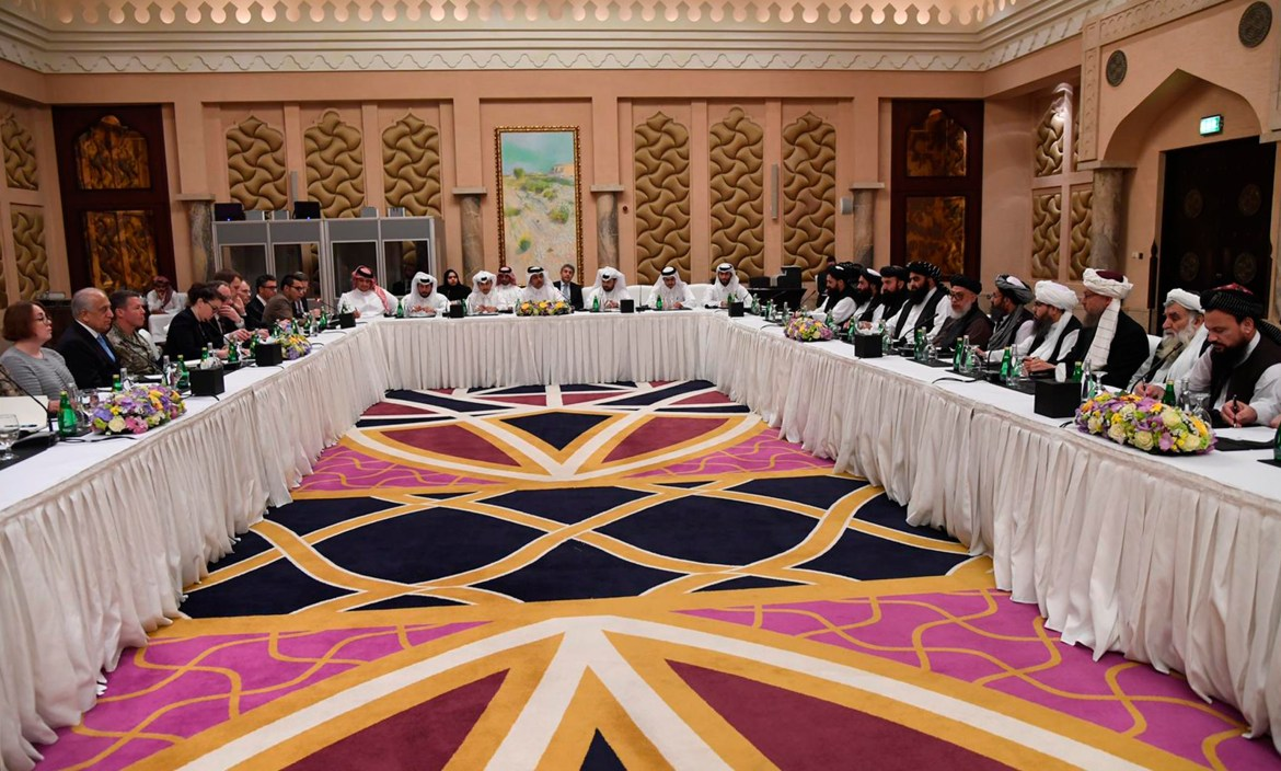 FILE - This Qatar Ministry of Foreign Affairs photo from Feb. 25, 2019, shows U.S. and Taliban representatives meeting in Doha to discuss ways to end the Afghan war.