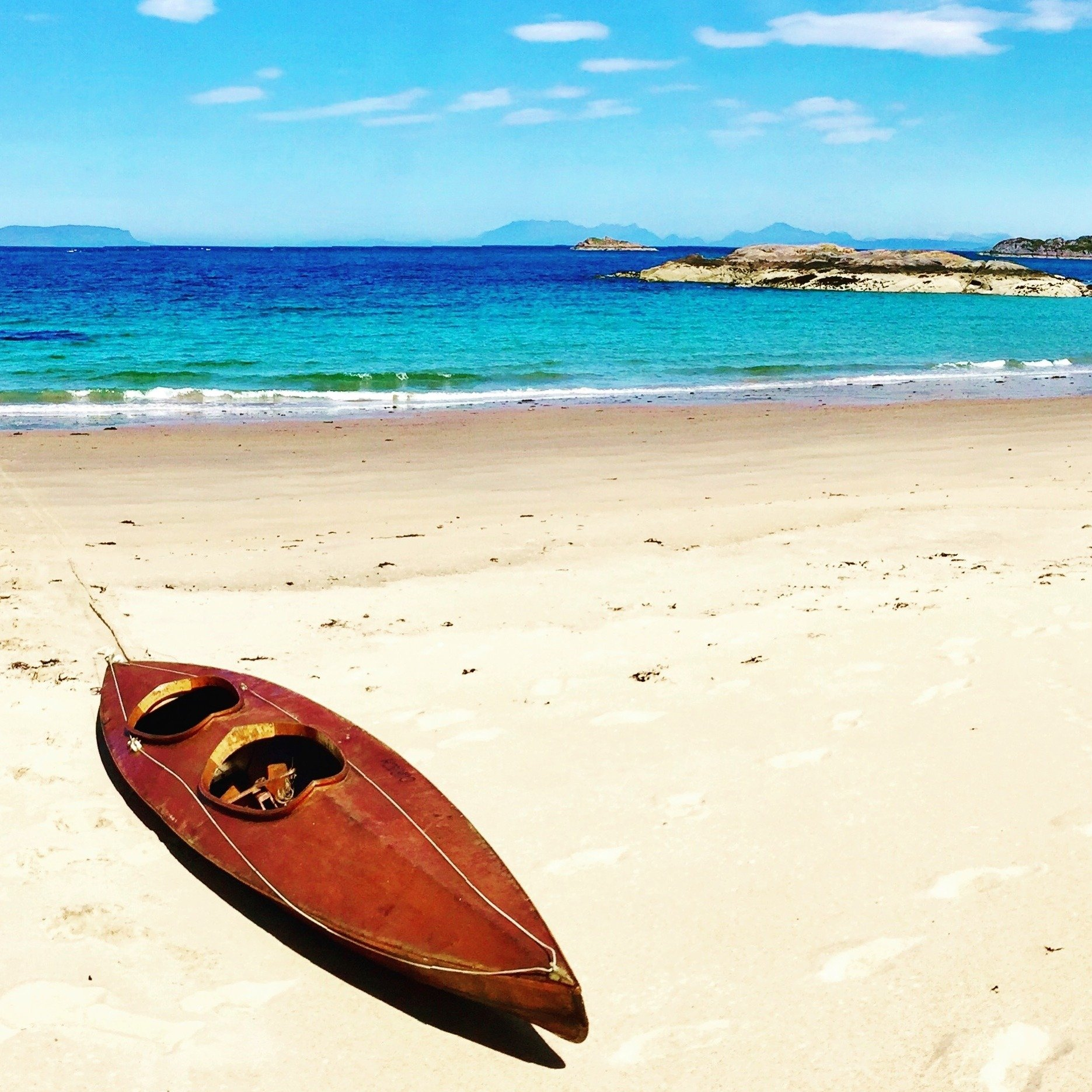 Wooden canoe on white sandy beach with turquoise sea Scotland