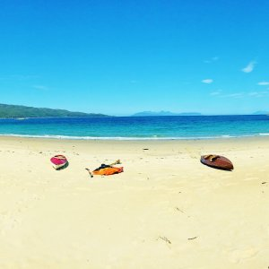 White sandy beach and turquoise sea with two kayaks in west Highlands of Scotland