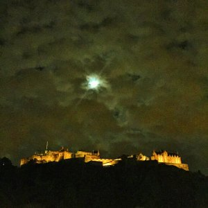 Edinburgh Castle lit up at night with moon shining
