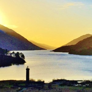Sunset over Scottish Loch Shiel surrounded by mountains with tall monument in foreground