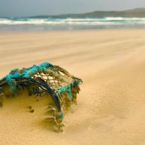 Lobster pot half-buried by sand on Scottish beach
