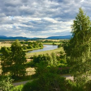 View of trees, fields and River Spey in evening sunlight, Cairngorms National Park, Scotland