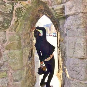 Student under ancient archway in royal university town of St Andrews, Scotland