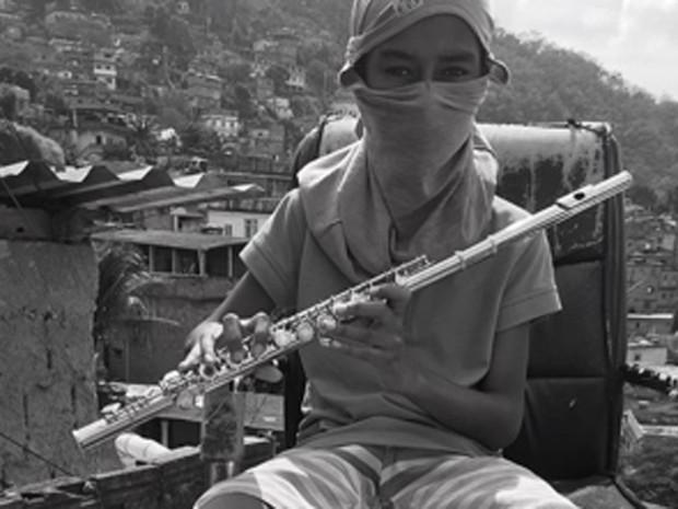 Menino toca instrumento musical na favela do Borel, na Tijuca (Foto: Anderson Valentim/Projeto Favelagrafia)