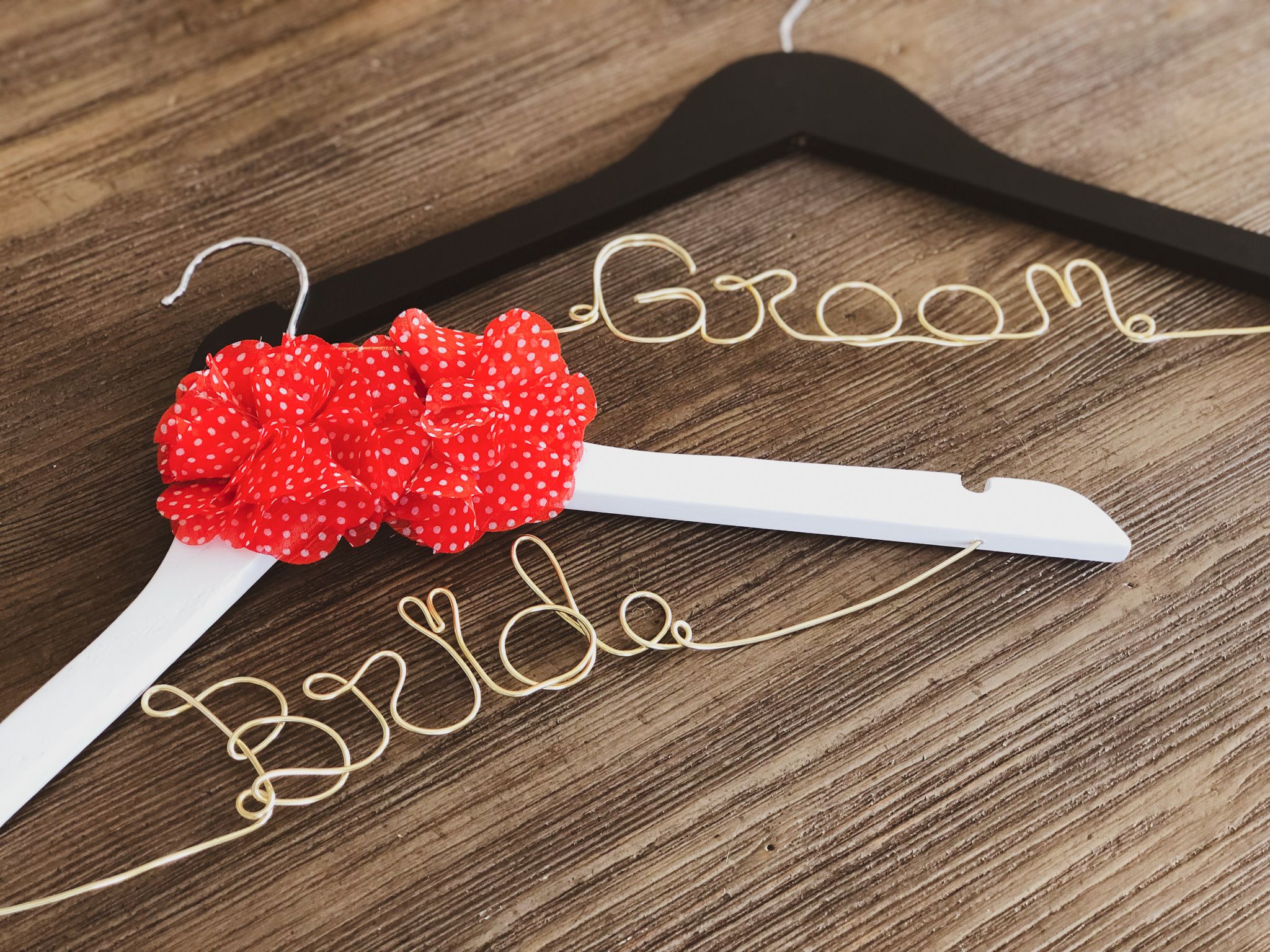 White Bride hanger with 2 Red and White Polkadot Flowers and Gold Wire, and Black Groom Hanger with Gold Wire