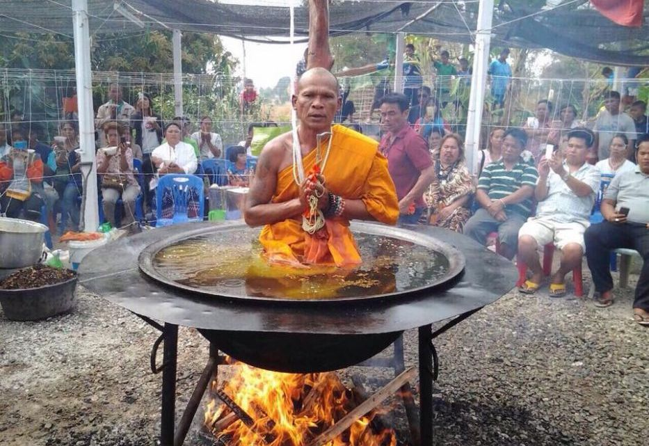 Thai monk meditates in a pot of boiling oil on fire