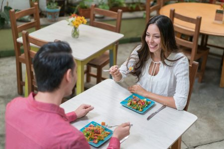 Healthy couple eating at a restaurant and looking very happy