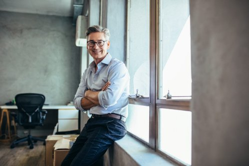 Smiling businessman looking at camera as he stands by a window sill with arms crossed. Mid adult businessman at his office.