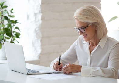 Mature businesswoman sitting at desk writing info thoughts on notepad, personal development get knowledge using internet sites, on-line research, teacher prepares for lesson, create to-do list concept