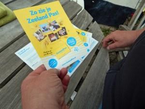 Tourist hält Werbezettel zum ZeelandPass in den Händen