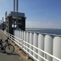 Ein Koloss aus Stahl: Das Wehr bei Vrouwenpolder zur Sicherung gegen Flutkatastrophen von der Straße mit FAhrrad im Anschnitt