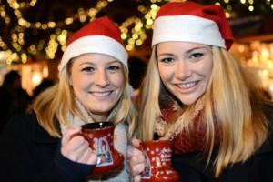 2 Frauen auf Weihnachtsmarkt mit Tassen für Heißgetränke