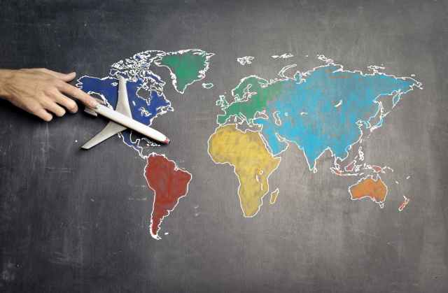 person with toy airplane on world map mercosur