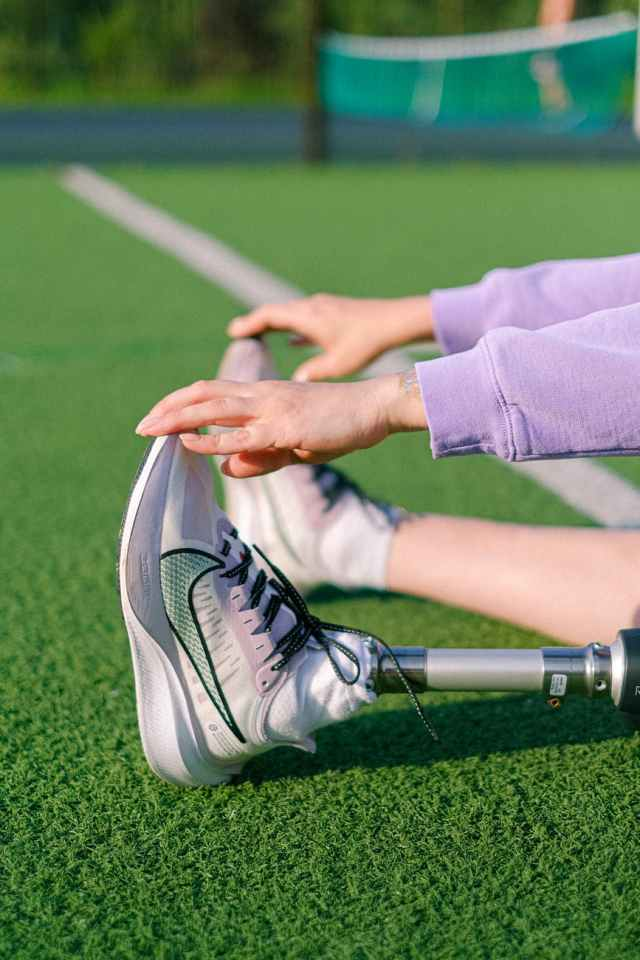crop disabled woman stretching on stadium agencia