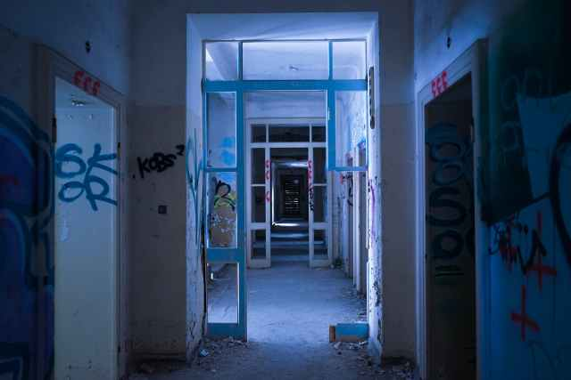 empty hall in abandoned shabby building with graffiti walls