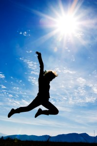 Person jumping with the sun, mountains, and a clear, blue sky in the background.