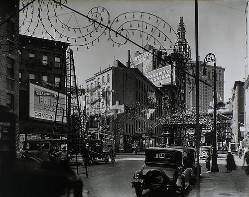 a street scene of billboards, decorative lights and old cars.
