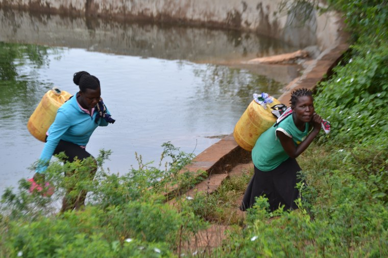women collecting water from rock water catchment reservoir, Kenya