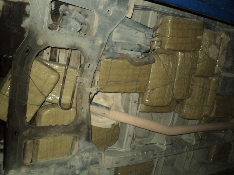 Paquetes con droga ocultos bajo el vehículo.