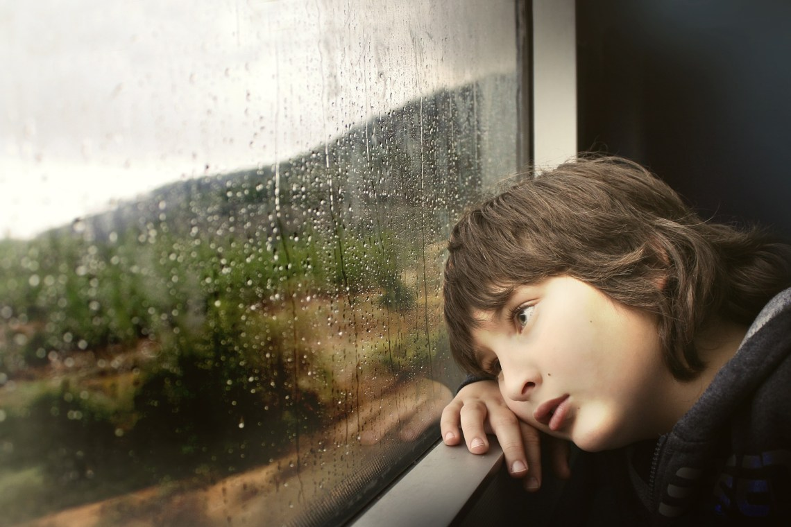Niño aburrido con lluvia