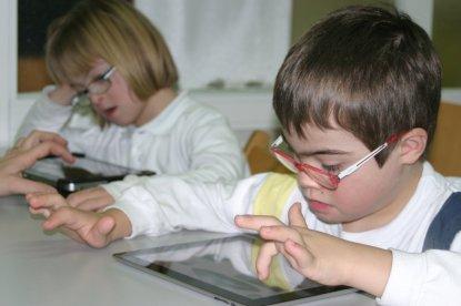 Niños con síndrome de Down en la escuela leen con una tablet