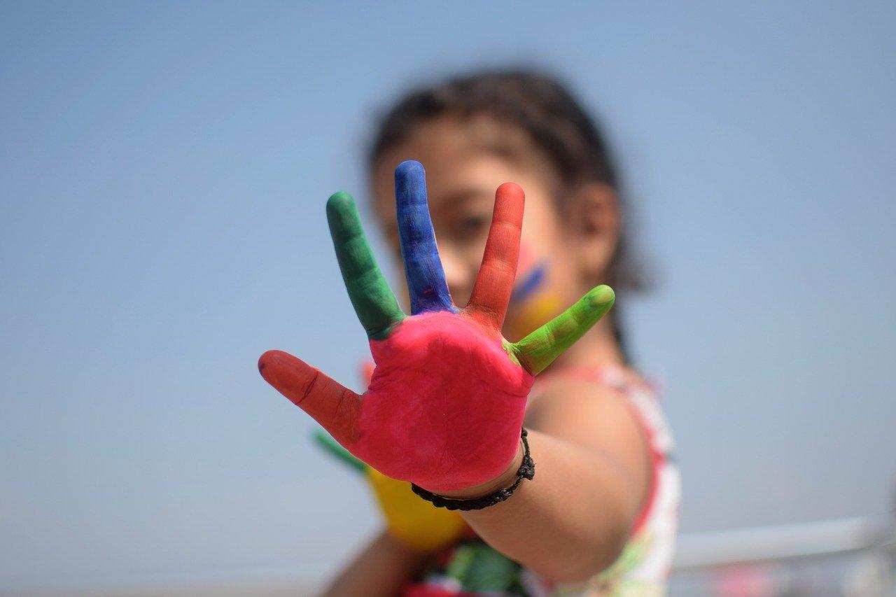 imagen que muestra una mano de niña pintada de muchos colores