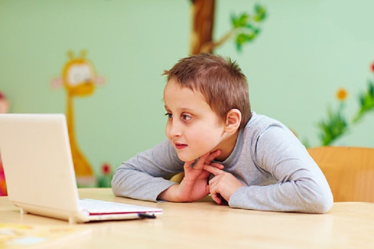 niño con discapacidad mira una computadora