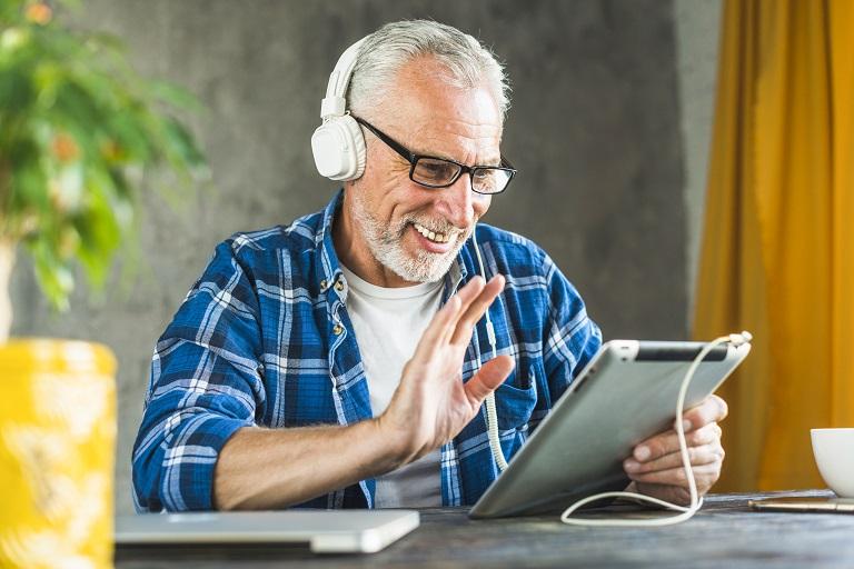 adulto mayor con tableta y auriculares