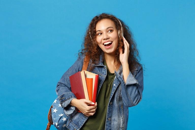 mujer joven con libros y auriculares