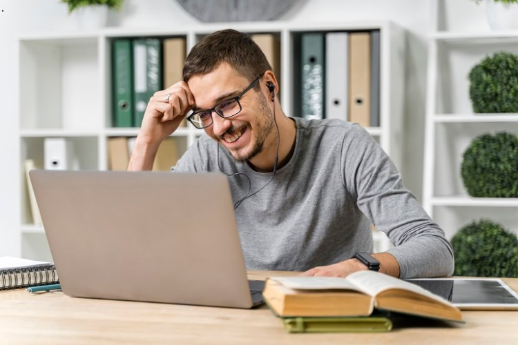 hombre joven con un ordenador, auricular y libros
