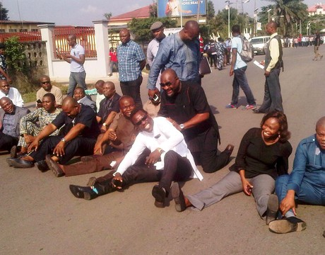 MEMBERS OF RIVERS HOUSE OF ASSEMBLY SITING ON MOSCOW ROAD, AFTER BEEN STOPPED FROM GAINING  ENTRANCE TO ASSEMBLY COMPLEX BY THE POLICE  IN PORT HARCOURT ON FRIDAY