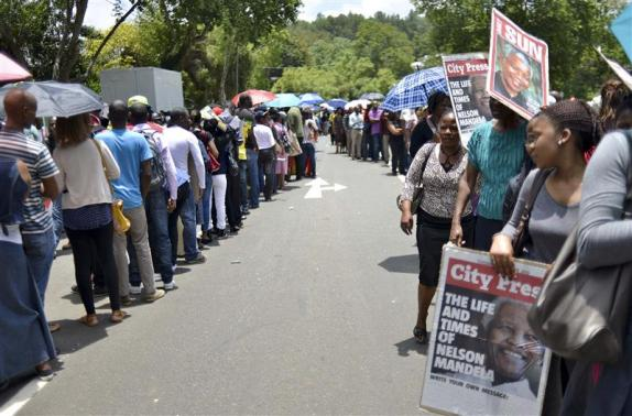 People wait for transport to take them to view the body of former South African President Nelson Mandela, who is lying in state, at the Union Buildings in Pretoria