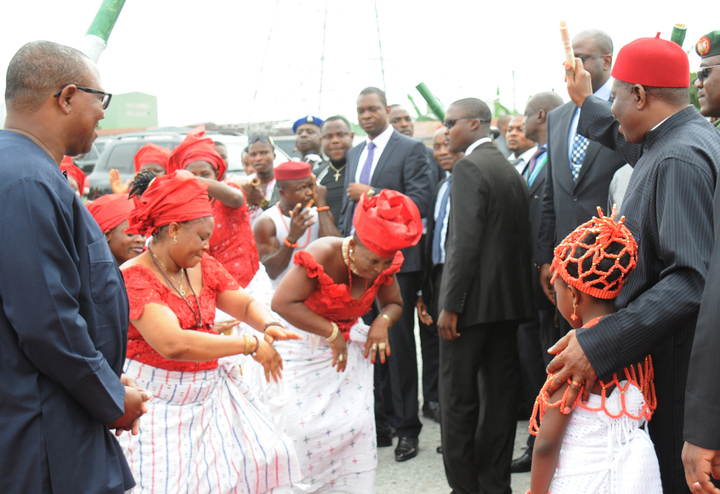 PRESIDENT GOODLUCK JONATHAN (R), ACKNOWLEDGING TRADITIONAL DANCERS HERALDING HIS ARRIVAL FOR THE GROUND BREAKING CEREMONY FOR  SECOND NIGER BRIDGE IN ONITSHA ON MONDAY (10/3/14). LEFT IS GOV. PETER OBI OF ANAMBRA.