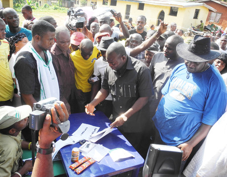 ANAMBRA PDP GOVERNORSHIP CANDIDATE, MR TONY NWOYE, EXPRESSING WORRY OVER THE DISAPPEARANCE OF HIS NAME, THAT OF HIS FATHER AND UNCLE FROM INEC VOTERS' REGISTER AT POLLING UNIT 004, OFIANTA, NSUGBE WARD ONE, ON SATURDAY (16/11/13) DURING  GOVERNORSHIP ELECTION.